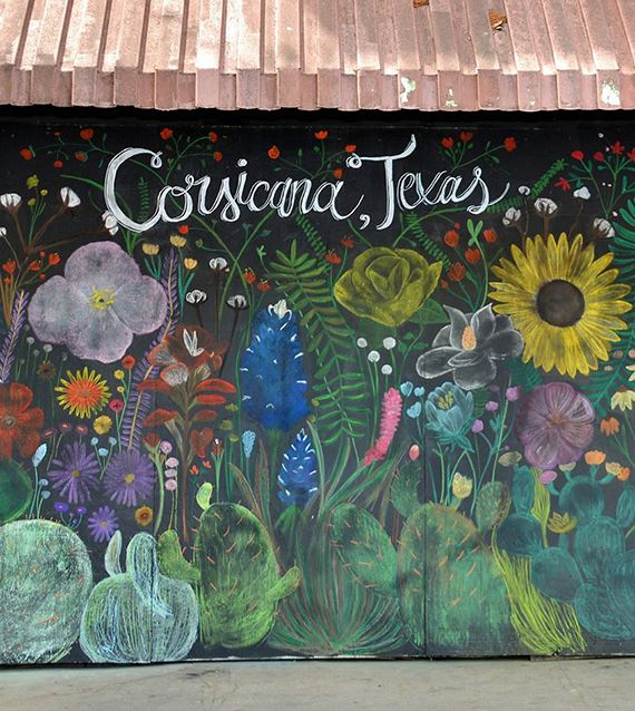 a side of a wall painted with flowers and the words with Corsicana Texas